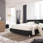 Juodai baltą miegamojo interjerą sušvelnina medinė spintelė ir komoda