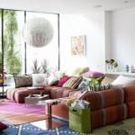 Svetainės interjeras, kuriame puikuojasi įvairiaspalvė kampinė sofa, krūva pagalvėlių, gėlės ir net trys skirtingi kilimai