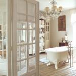 Masyvus sietynas ir grakščios formos pastatoma vonia