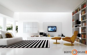 Baldai prie televizoriaus tarsi susilieja su balta siena, tad geltonas fotelis su pakoju ir knygų lentyna bei tiesių linijų kilimas tampa atsvara