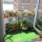 Palei balkono turėklus surykiuoti vazonėliai dvejais aukštais