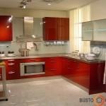 Raudonuose virtuvės balduose langas, paslėptas po užuolaidomis, tarsi pranyksta