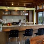 Virtuvės erdvė prie ištisinės vitrininių langų eilės