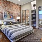 Ant sendintų plytų sienos dizaineriai paveikslus rekomenduoja ne kabinti, o statyti ant žemės ar baldų, taip sustiprinamas neužbaigtumo jausmas