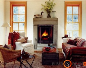 Šiltų spalvų lovatiesė ir degantis židinys suteikia rudeniško jaukumo kambariui