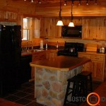 Virtuvės baldai tarsi įsilieja į medines sodybos sienas