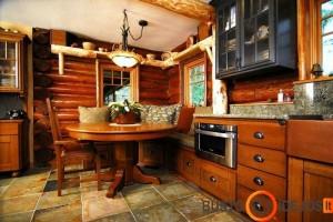 Virtuvės baldai spalviškai priderinti prie rąstinės sodybos sienos
