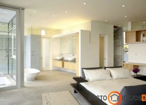 Neįprastas baldų išdėstymas miegamajame su vonia