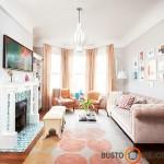 Pastelinis oranžinis klasikinio stiliaus kambarys su marokietiškais suoliukais ir Viduržemio jūros stiliaus židiniu